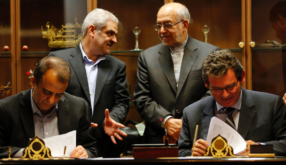 Deputy of France's Peugeot Citroen (PSA) Jean-Christophe Quemard,(R) signs documents with CEO of industrial group Iran Khodro, Hachem Yekehzare (L), as Iran's Industry and Commerce Minister Mohammad Reza Nematzadeh (2R) watches on in Tehran on June 21, 2016. PSA is the first Western carmaker to announce a return to Iran since many economic sanctions were lifted in January when a landmark nuclear deal with world powers took effect. / AFP / ATTA KENARE (Photo credit should read ATTA KENARE/AFP/Getty Images)